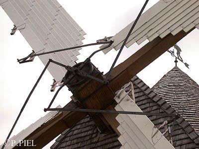 """Système Berton qui équipe bon nombre de moulins saintongeais à partir de la deuxième moitié du XIX° siècle.  A noter le croisillon qui porte """"l'araignée"""", ensemble de leviers qui tirent et déploient les bras extensibles commandant l'ouverture des ailes.   De plus, on voit ici les essendes, tuiles de bois taillées en ardoises qui  couvrent le toit du moulin. Moulin de Jonzac, juin 2004."""